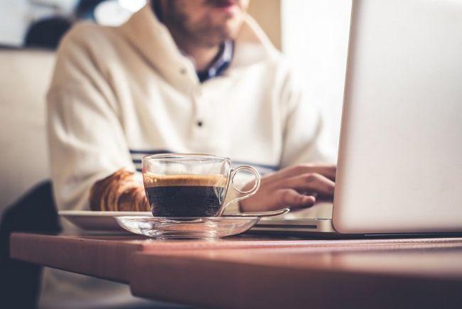homem no laptop usando wi-fi pública no café