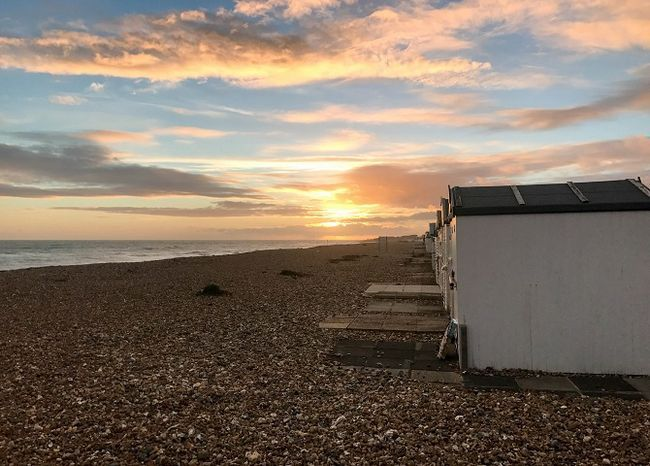 pôr do sol na praia com galpões