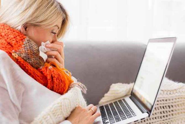 mulher doente que trabalha no portátil